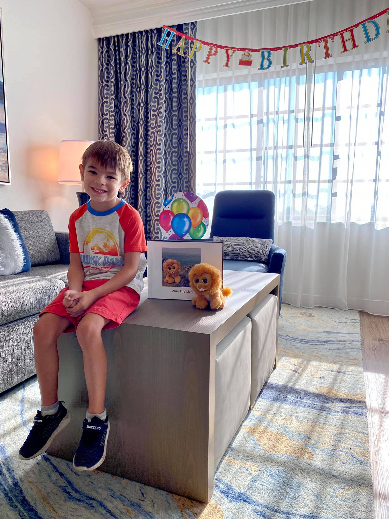 Jax and Little Louie posing with the book in their birthday decorated suite at Hilton Grand Vacations at MarBrisa in Carlsbad, California.