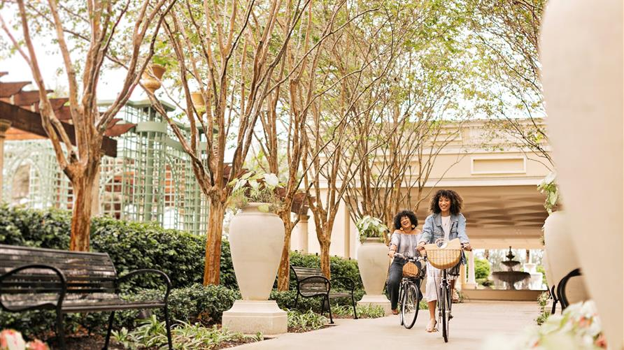 Two women staying at a Hilton Grand Vacations Orlando resort smiling on carefree bike ride on property.