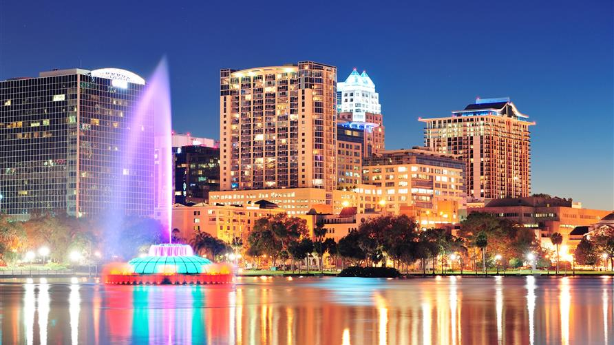 Lake Eola fountain and Orlando skyline lit up at night.