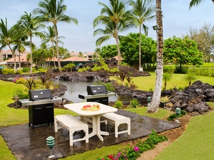 Barbeques and picnic tables surrounded by lush landscaping at The Bay Club Waikoloa Beach Resort.