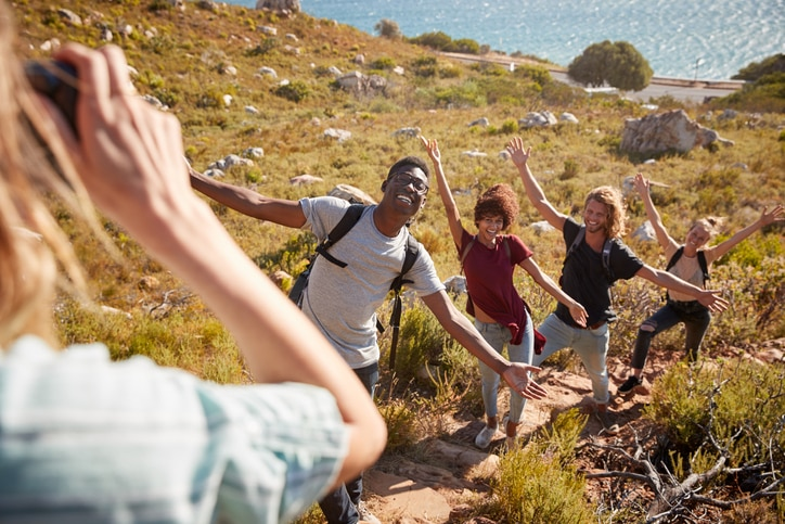 A group of young adults smiling posing with their arms up while on vacation.