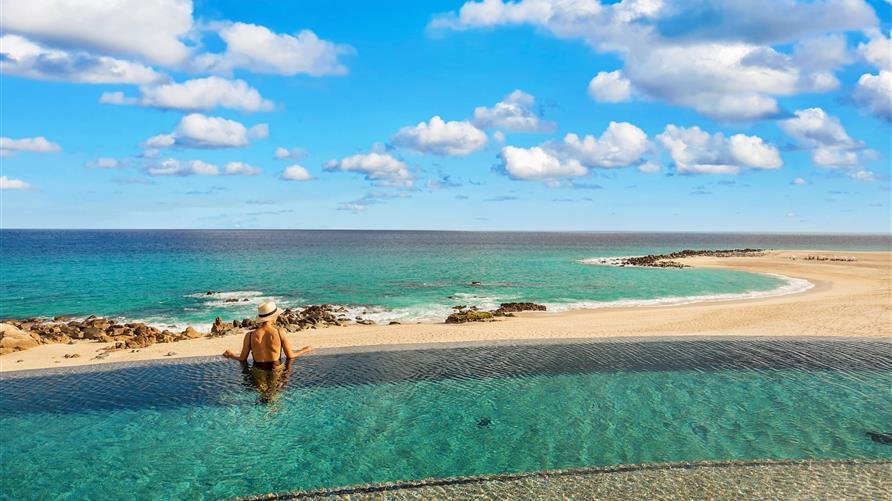 Woman gazing into the Sea of Cortez from the infinity pool at La Pacifica by Hilton Club in Los Cabos, Mexico.