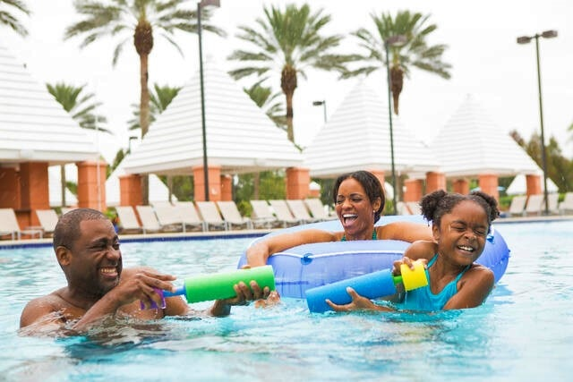 Family playing in the pool with floats and water sprayers at Hilton Grand Vacations at SeaWorld in Orlando, Florida.