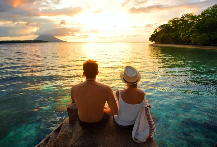 Couple on a romantic getaway enjoying the sunset overlooking the water.