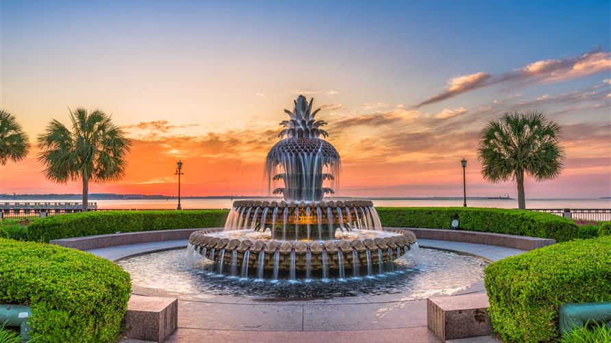 The Pineapple Fountain in Charleston, South Carolina with orange painted sunset skies behind.