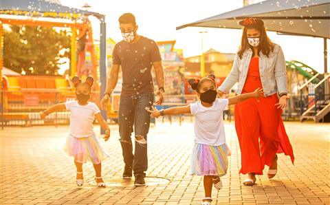 Family wearing masks and playing in bubbles in a theme park in Orlando, Florida.