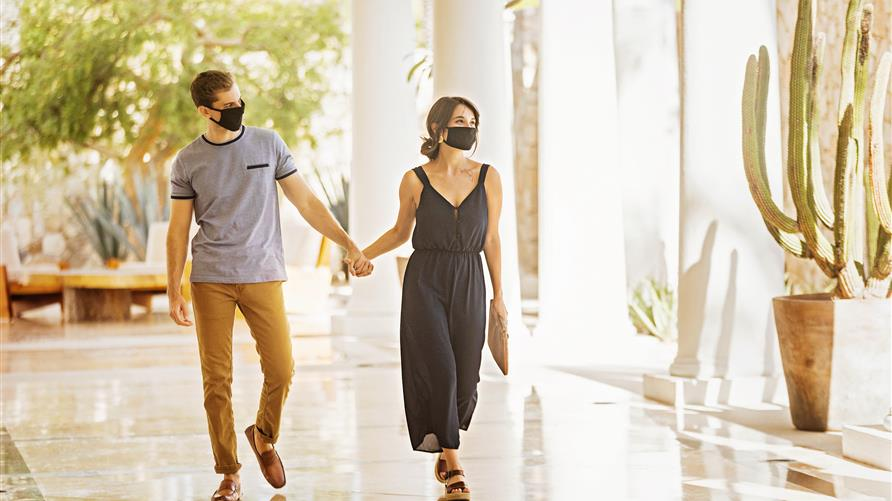 Couple wearing face coverings and holding hands while walking through a breezeway at Los Cabos by Hilton Club in Los Cabos, Mexico.