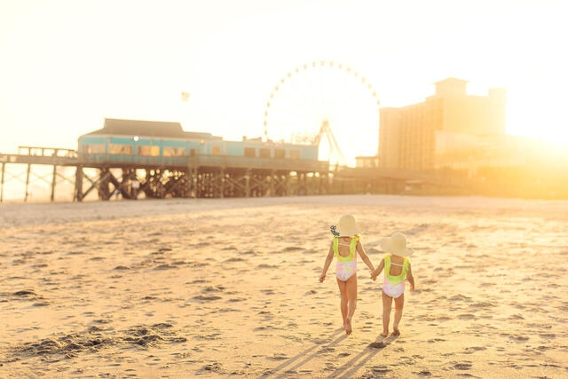 Two young girls holding hands while walking along Myrtle Beach, South Carolina.