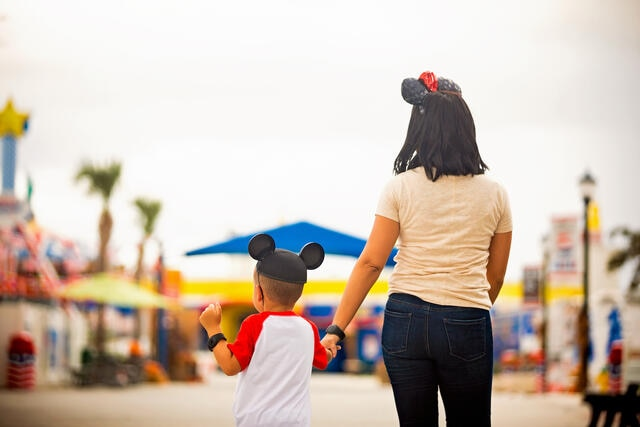 Mother and son walking hand in hand wearing Micky Mouse ears while on vacation in Orlando, Florida.