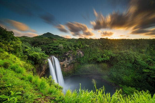 Breathtaking waterfall with blue and orange painted skies above in Maui, Hawaii.