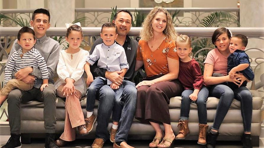 Family vacation photo at Elara, a Hilton Grand Vacations Club in Las Vegas after couple adopts seven siblings in foster care.