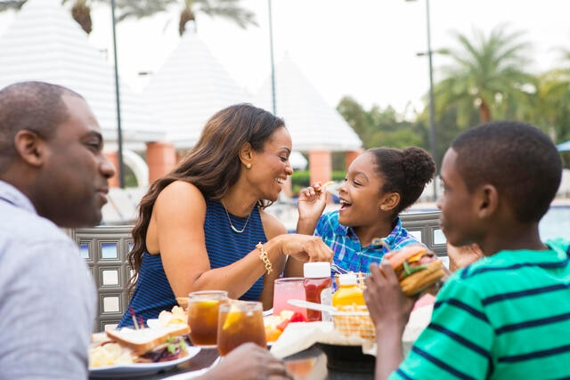 Family enjoying a meal together poolside at Hilton Grand Vacations at SeaWorld resort in Orlando.