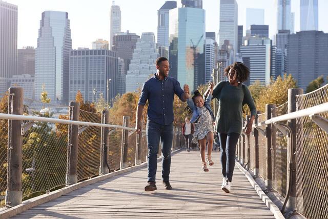 Family of three joyfully walking across an the High Line in New York City.