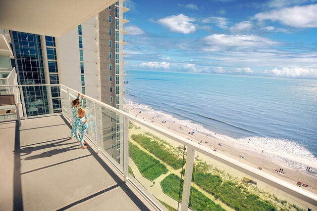 Young girls in pajamas looking out to sea on a Hilton Grand Vacations Myrtle Beach resort private balcony.