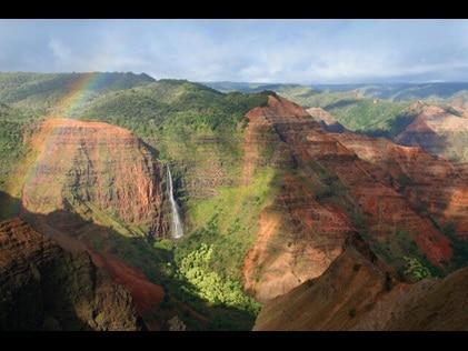 Rainbow  and waterfall in Waimea Canyon State Park in Hawaii.