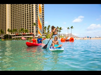 Family paddle boarding in the Hilton Hawaiian Village lagoon while on vacation in Hawaii.