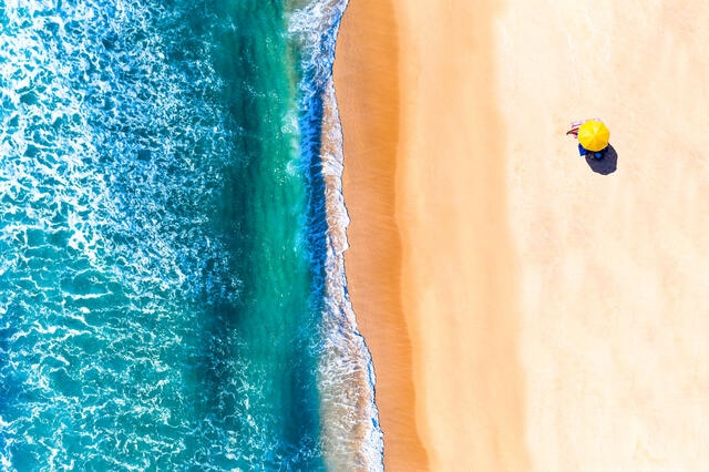 Aerial view of a yellow beach umbrella on the shoreline.
