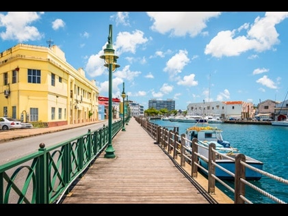 Shot of Bridgetown Boardwalk with buildings on one side and water and boats on the other in Barbados.