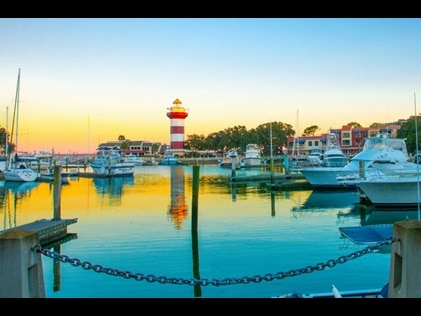 Boat Marina at with light house in the distance at sunset on Hilton Head island, South Carolina.