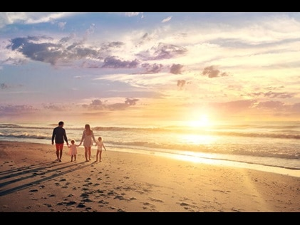 Family of four walking hand in hand at sunset on Myrtle Beach in South Carolina.