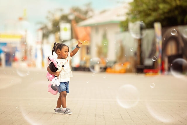 Little girl holding Mini Mouse and playing with bubbles while on vacation in Orlando, Florida.