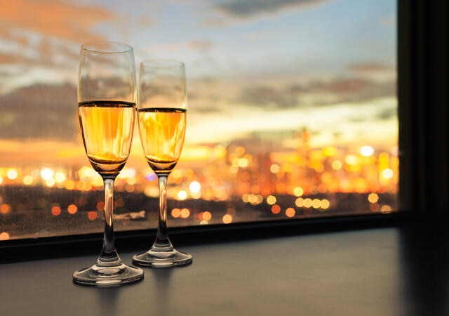 Two glasses of wine on a window ledge with city lights in the distance.