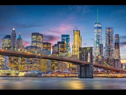 New York City skyline glowing against the night sky.