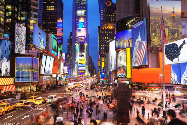 Times Square Plaza lit up at nighttime in New York City.