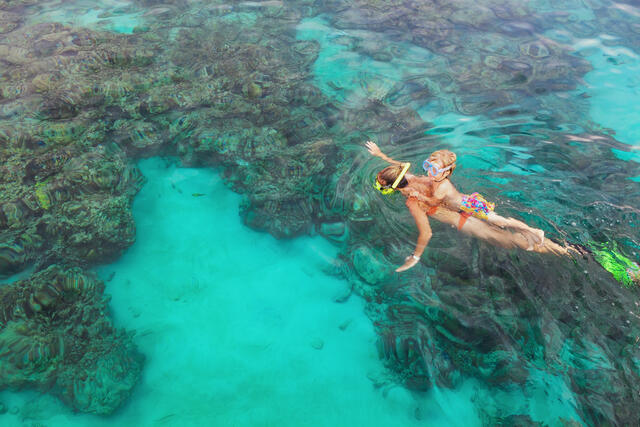 Mom and child snorkeling above coral reef in emerald green water.