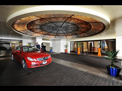 Red Mercedes rental car at the Valet at Hilton Grand Vacations exchange resort, Club Donatello in San Francisco, California.