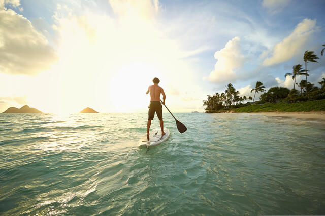 Man stand up paddle boarding while on vacation.