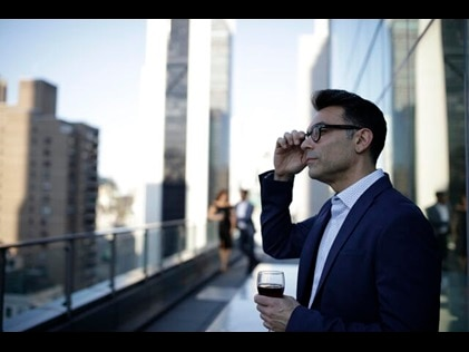 Man enjoying a beverage while taking in the New York City Skyline from the Owners Terrace at West 57th Street by Hilton Club, a New York City timeshare.