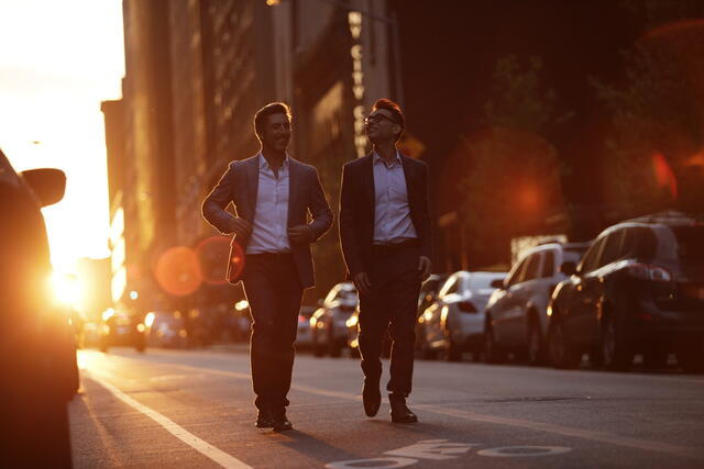 Two men walking down Midtown Manhattan street at sunset in New York City.