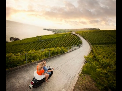 Aerial shot of a couple riding a scooter along a country road in Tuscany, Italy.