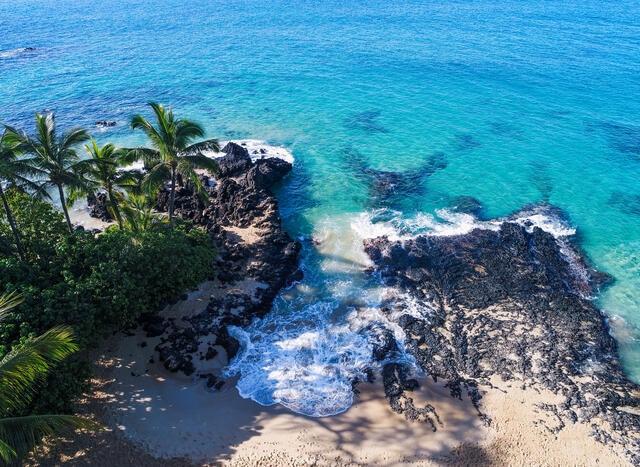 Aerial shot of turquois waves crashing against black rocks on Maui in Hawaii.