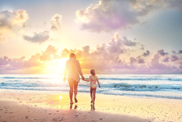 Mother and daughter on beach admiring the sunset.