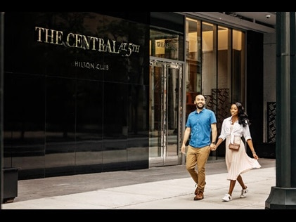 Couple walking hand in hand outside The Central at 5th by Hilton Club in Midtown Manhattan, New York City.