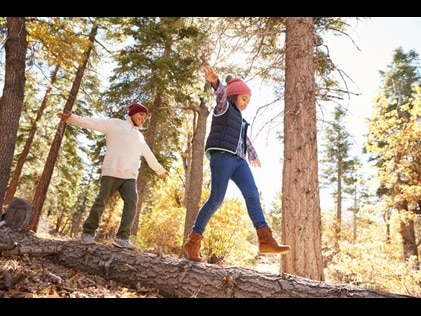 Kids playing on a log surrounded by fall foliage.