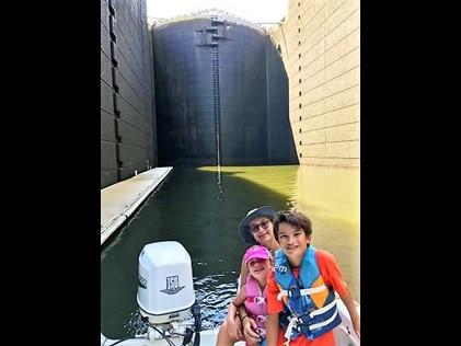 Kids in a boat posing at Pinopolis Locks in Charleston, South Carolina.
