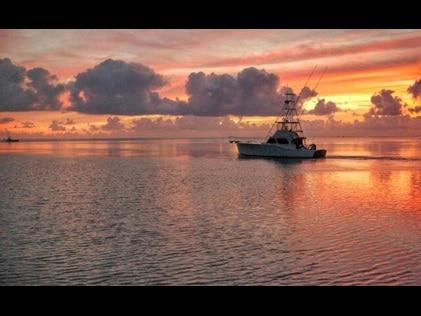 Silhouette of fishing boat on Charleston, South Carolina, waterway at sunset.