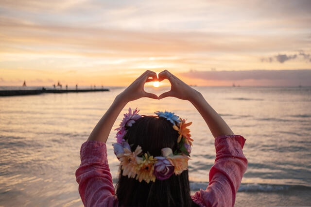 Woman wearing a flower crown and making heart hands toward the sunset in Hawaii.