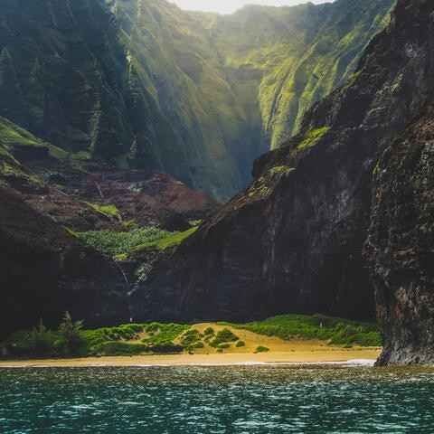 Sun shining through mountain lined beach in Hawaii.