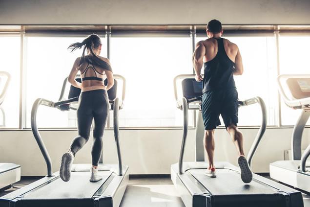 man and women running on treadmill