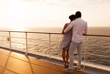 Couple on the upper deck of a cruise ship watching the sunset.