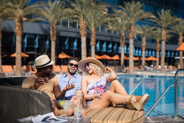Group laughs together as they sit poolside with their drinks.