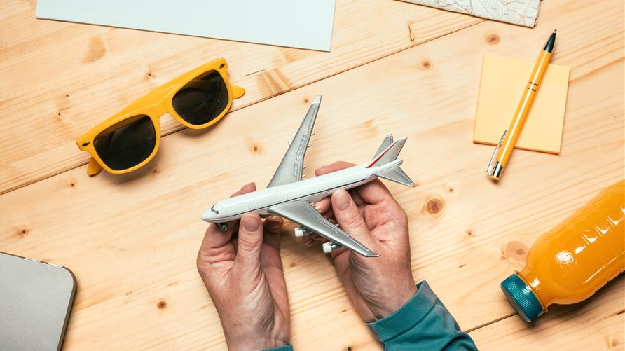 Overhead shot of a man holding a toy airplane with a notepad and pencil nearby.
