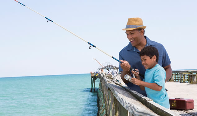 father and son fishing off pier