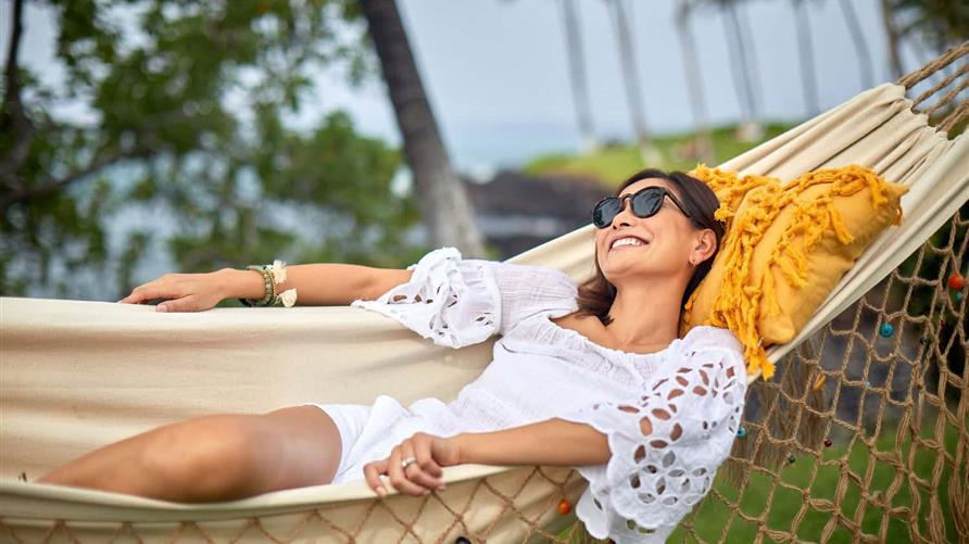 Woman smiling while  lounging in a hammock.