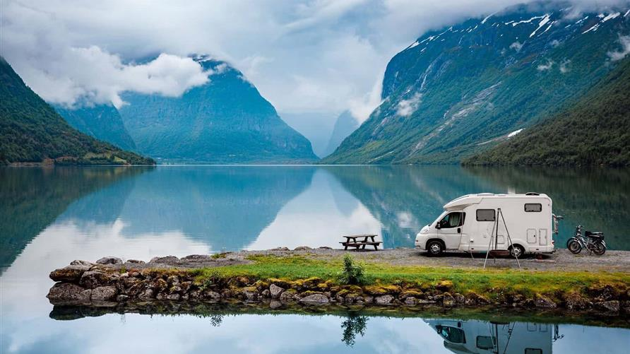 Picture of an RV next to a lake with the mountains in the distance.