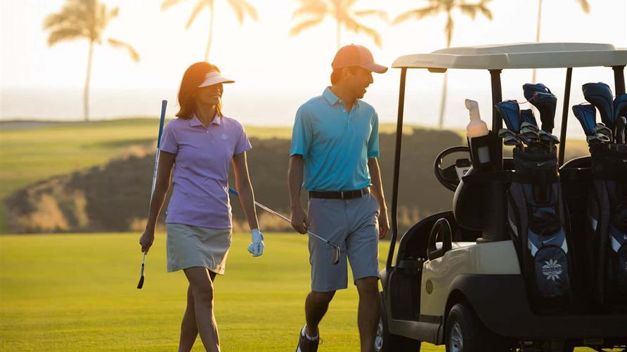 Couple walking on a golf course in Hawaii while on vacation with Hilton Grand Vacations.